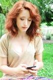 Giovane donna che per mezzo del telefono Immagini Stock