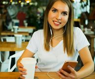 Giovane donna che per mezzo del telefono cellulare al caffè Immagine Stock