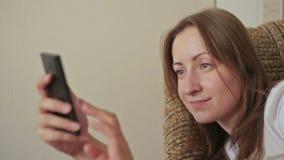 Giovane donna che per mezzo del telefono cellulare a casa video d archivio