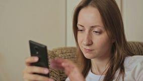 Giovane donna che per mezzo del telefono cellulare a casa stock footage