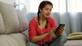 Giovane donna che per mezzo del telefono per ascoltare musica stock footage