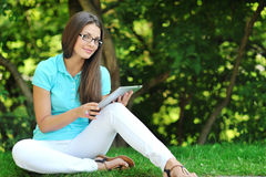 Giovane donna che per mezzo della compressa digitale Immagini Stock Libere da Diritti