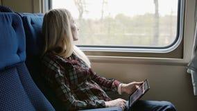 Giovane donna che per mezzo della compressa mentre viaggiando in treno stock footage