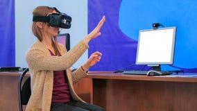 Giovane donna che per mezzo della cuffia avricolare di realt? virtuale davanti al monitor in bianco bianco immagini stock libere da diritti