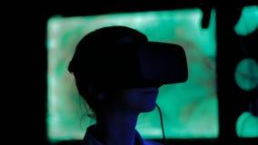Giovane donna che per mezzo della cuffia avricolare di realt? virtuale alla mostra interattiva scura archivi video