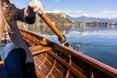 Giovane donna che per mezzo della pagaia su una barca di legno con il castello sanguinato dietro - rematura della Slovenia sangui fotografia stock libera da diritti