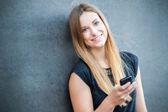 Giovane donna che per mezzo dello Smart Phone Immagine Stock