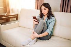 Giovane donna che per mezzo dello smartphone a casa fotografie stock