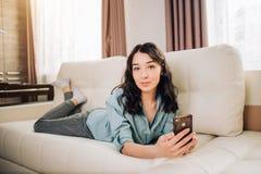 Giovane donna che per mezzo dello smartphone a casa fotografia stock