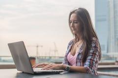 Giovane donna che per mezzo di un computer portatile che funziona all'aperto Femminile esaminando lo schermo e scrivendo sulla ta Immagine Stock Libera da Diritti