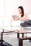 Giovane donna che per mezzo di un PC della compressa sul sofà fotografie stock libere da diritti