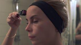 Giovane donna che per mezzo di un rullo di derma per il micro fronte di terapia di agugliatura video d archivio