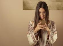 Giovane donna che per mezzo di un telefono mobile immagini stock