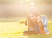 Giovane donna che per mezzo di una compressa all'aperto Fotografia Stock