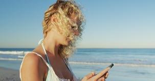 Giovane donna che per mezzo di uno smartphone alla spiaggia 4k video d archivio