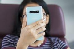 Giovane donna che per mezzo di uno smartphone di Samsung fotografia stock