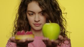 Giovane donna che pesa mela e dolce in mani in studio giallo stock footage