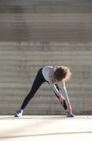 Giovane donna che piega giù l'allungamento dei muscoli della gamba Immagini Stock
