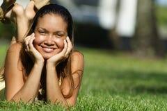 Giovane donna che pone sull'erba Fotografie Stock Libere da Diritti