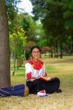 Giovane donna che porta i vetri tradizionali, gonna andina e blusa con l'accoppiamento della collana rossa, sedentesi sull'erba a Fotografia Stock