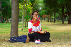 Giovane donna che porta i vetri tradizionali, gonna andina e blusa con l'accoppiamento della collana rossa, sedentesi sull'erba a Immagini Stock Libere da Diritti