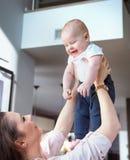 Giovane donna che porta suo figlio sveglio immagini stock