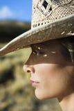 Giovane donna che porta un cappello di cowboy della paglia. Immagine Stock