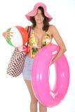 Giovane donna che porta un vestito di nuotata in vacanza che porta un beach ball Fotografia Stock Libera da Diritti
