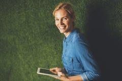 Giovane donna che posa con la compressa dalla parete verde fotografia stock libera da diritti