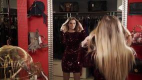 Giovane donna che posa davanti ad uno specchio in un deposito, sceglie un vestito archivi video