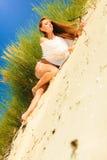 Giovane donna che posa in duna erbosa Immagini Stock