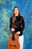 Giovane donna che posa nello studio che tiene una chitarra classica Fotografie Stock Libere da Diritti