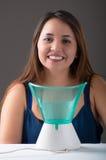 Giovane donna che posa per la macchina fotografica dietro di una macchina medica del nebulizzatore del vaporizzatore su fondo gri Fotografia Stock Libera da Diritti