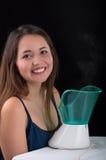 Giovane donna che posa per la macchina fotografica dietro di una macchina medica del nebulizzatore del vaporizzatore su fondo ner Fotografia Stock Libera da Diritti