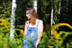 Giovane donna che posa sui precedenti, i cespugli della priorità alta Fotografia Stock