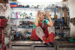 Giovane donna che posa in un negozio del meccanico Fotografie Stock