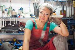 Giovane donna che posa in un negozio del meccanico Immagini Stock Libere da Diritti