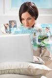 Giovane donna che pratica il surfing sul web con il computer portatile moderno Fotografie Stock