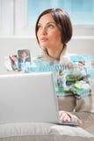 Giovane donna che pratica il surfing sul web con il computer portatile moderno Fotografia Stock