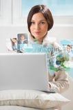 Giovane donna che pratica il surfing sul web facendo uso del computer portatile moderno Fotografie Stock Libere da Diritti