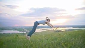 Giovane donna che pratica vibrazione acrobatica attraverso il sole al tramonto archivi video