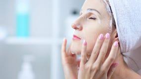 Giovane donna che prende cura della pelle del fronte con la maschera cosmetica del tessuto, concetto del primo piano archivi video