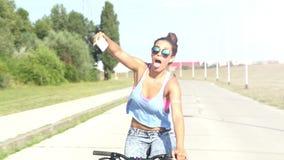 Giovane donna che prende i selfies svegli mentre ciclare, classificato video d archivio