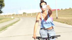 Giovane donna che prende i selfies svegli mentre ciclare, classificato archivi video