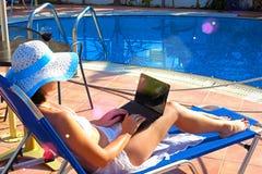 Giovane donna che prende il sole sulla sedia a sdraio con il computer portatile Fotografia Stock