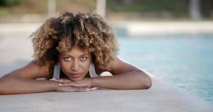 Giovane donna che prende il sole vicino alla piscina stock footage
