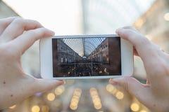 Giovane donna che prende immagine sullo smartphone del centro commerciale fotografia stock