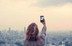 Giovane donna che prende la foto di tramonto immagine stock