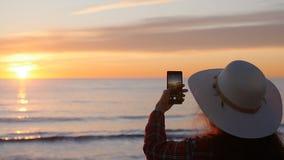 Giovane donna che prende le foto sulla spiaggia durante il tramonto o l'alba stock footage