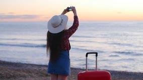 Giovane donna che prende le foto sulla spiaggia durante il tramonto o l'alba video d archivio